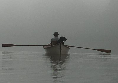A man and his boat enjoying a foggy morning on a local lake.