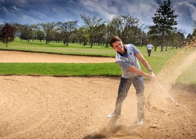 A golfer tries to escape a sandtrap at the Penn State Golf Courses.